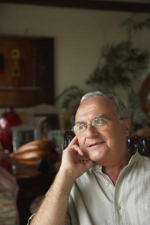 Senior Hispanic man sitting in chair