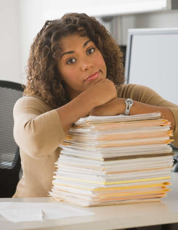 babyboomer: African businesswoman leaning on stack of paperwork