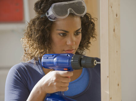 bathtowel: African woman using cordless drill