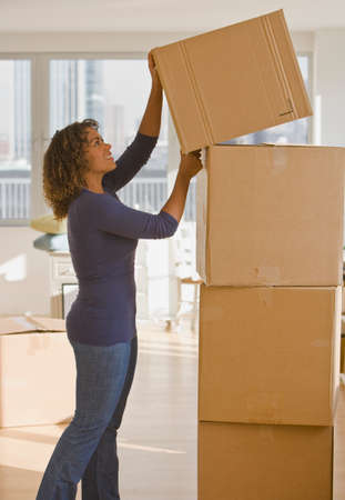 acknowledging: African woman stacking moving boxes LANG_EVOIMAGES