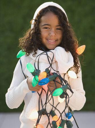 relishing: African girl holding Christmas lights