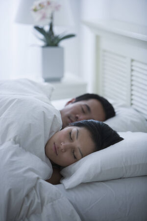 woman bathrobe: Asian couple sleeping in bed