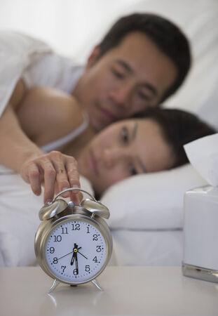 slumbering: Asian man touching alarm clock LANG_EVOIMAGES