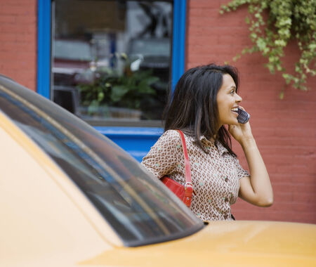 streetlife: Mixed Race woman talking on cell phone LANG_EVOIMAGES