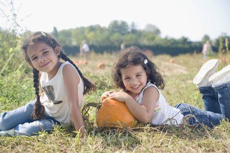 wearying: Hispanic sister sitting next to pumpkin
