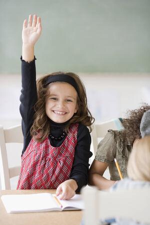 portraiture: Girl raising hand in class LANG_EVOIMAGES