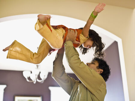 indian ethnicity: Indian father holding daughter in air