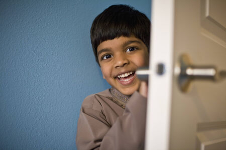 flowergirl: Indian boy laughing behind door LANG_EVOIMAGES