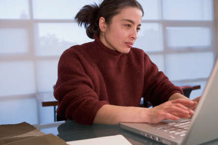 Mixed Race woman typing on laptop Stock Photo