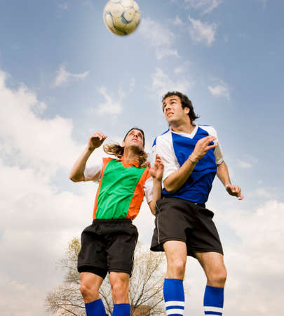 Multi-ethnic male soccer players jumping for ball Stock Photo