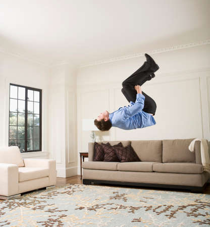 level playing field: Hispanic businessman doing flip in livingroom LANG_EVOIMAGES