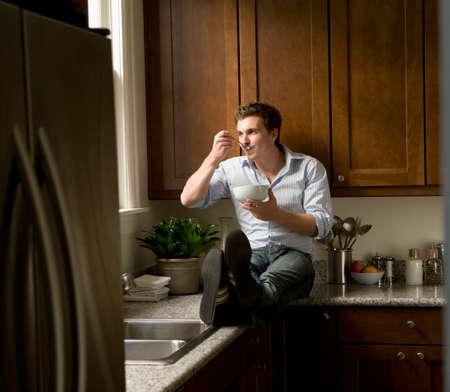 slumbering: Hispanic man eating on kitchen counter