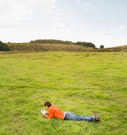 exerting: Hispanic boy playing handheld video game in field