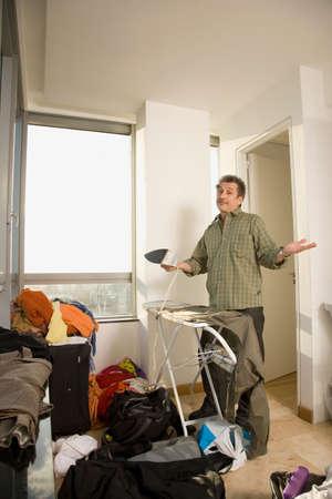 rd: Man shrugging shoulders in messy room LANG_EVOIMAGES