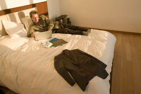 dwelling mound: Man looking at laptop on bed LANG_EVOIMAGES