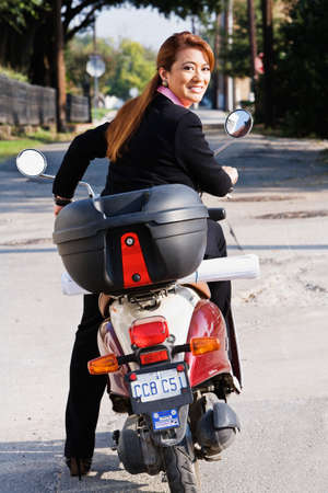 pacific islander ethnicity: Asian businesswoman riding motor scooter