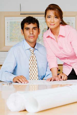 attired: Multi-ethnic businesspeople next to blueprints