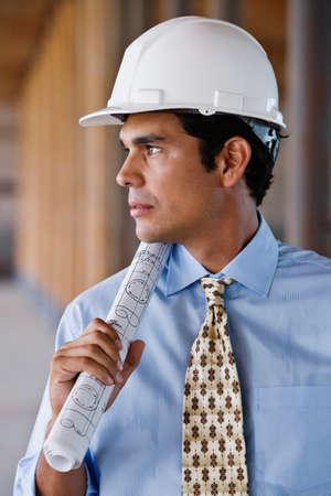 hard: Hispanic businessman wearing hard hat LANG_EVOIMAGES