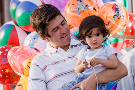 longshot: Hispanic father holding son with balloons LANG_EVOIMAGES