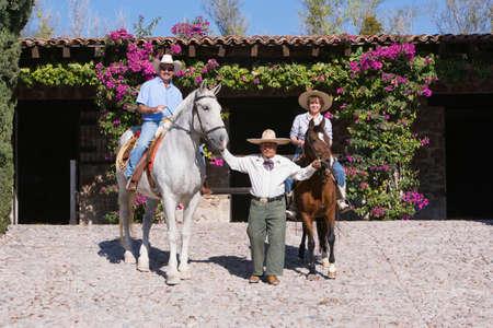 full length herbivore: Hispanic man leading couple on horses