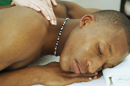 ostentatious: African man receiving massage LANG_EVOIMAGES