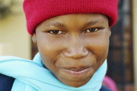 attired: African boy wearing winter hat and scarf