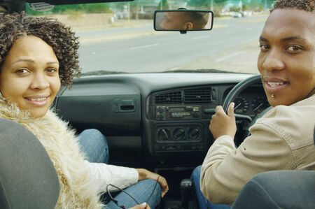 African couple driving in convertible car Stock Photo