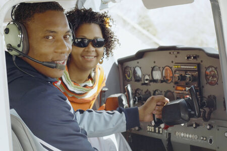African couple in cockpit of airplane Фото со стока