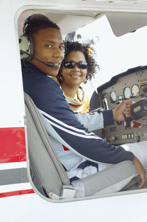 adventuresome: African couple in cockpit of airplane LANG_EVOIMAGES
