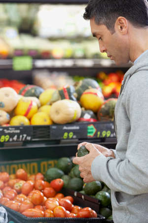 mid life: Hispanic man shopping for produce LANG_EVOIMAGES