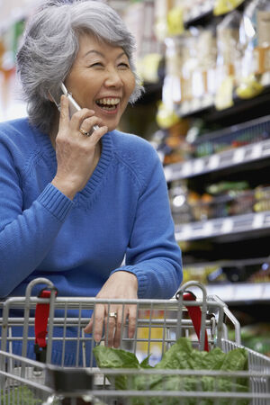 only one young adult woman: Senior Asian woman talking on cell phone LANG_EVOIMAGES