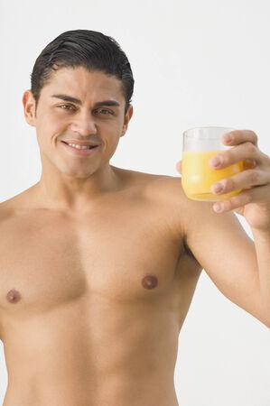 barechested: Bare-chested Hispanic man holding orange juice LANG_EVOIMAGES
