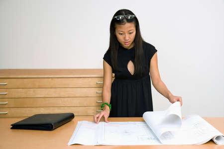 talker: Asian businesswoman looking at blueprints LANG_EVOIMAGES