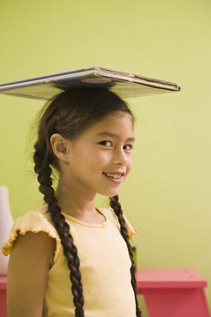 light hearted: Pacific Islander girl balancing book on head