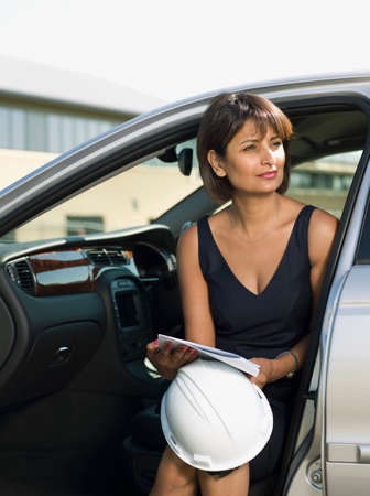 transportation: Indian woman holding hard hat in car LANG_EVOIMAGES