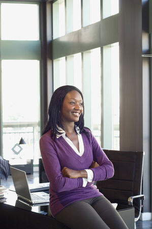 african american woman business: African businesswoman sitting on edge of desk LANG_EVOIMAGES