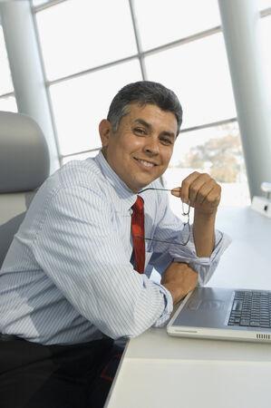 mid life: Hispanic businessman holding eyeglasses