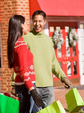 relishing: Asian couple carrying shopping bags