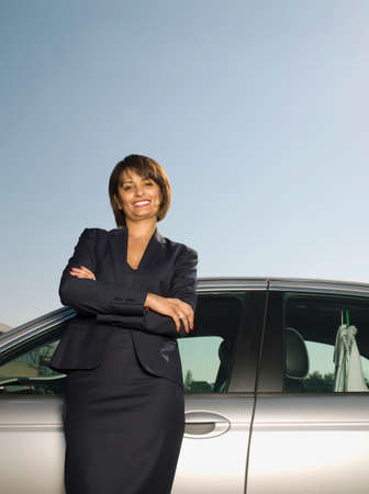 self indulgence: Indian businesswoman leaning on car