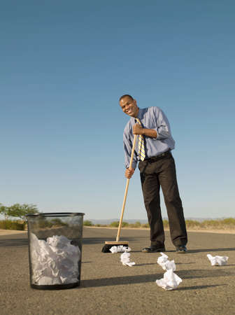 longshot: African businessman sweeping up paper in road