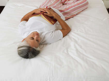 mid life: Asian woman sleeping with book