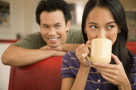 pacific islander ethnicity: Asian man watching woman drink coffee