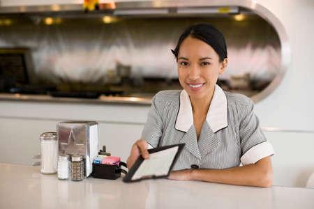 bringing: Asian waitress holding out bill