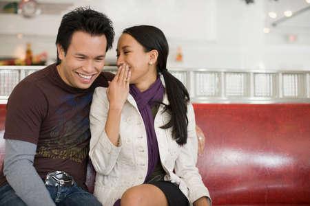 davenport: Asian woman telling boyfriend a secret LANG_EVOIMAGES