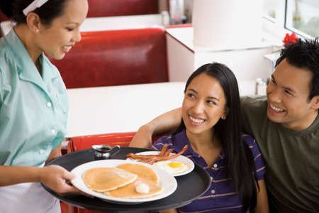 relishing: Asian couple being served food at diner LANG_EVOIMAGES