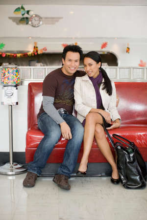 Asian couple sitting on sofa