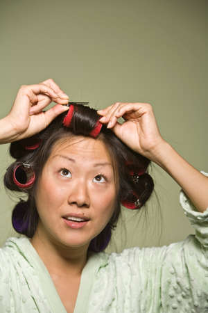 oriental bathrobe: Asian woman putting curlers in hair LANG_EVOIMAGES
