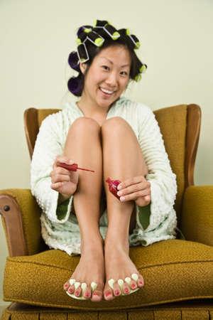 motioning: Asian woman painting toenails