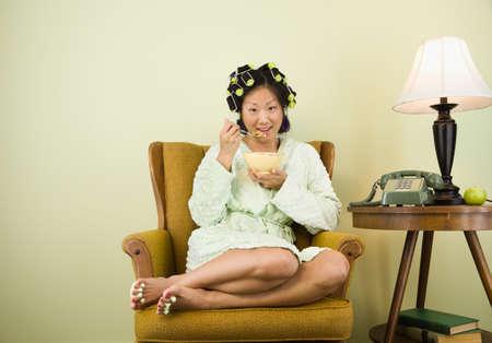 comiendo cereal: Mujer asi�tica en rulos comer cereales