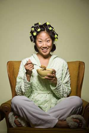 oriental bathrobe: Asian woman in curlers eating cereal LANG_EVOIMAGES